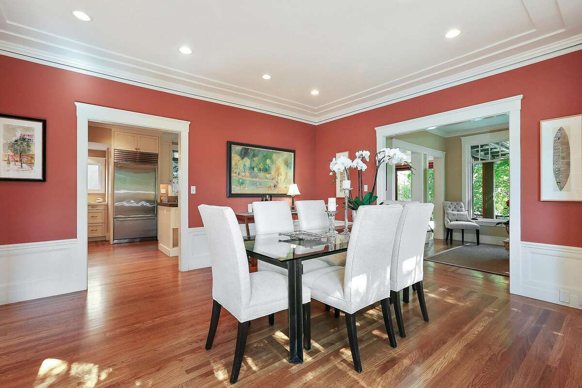 Wainscoting and a dramatic color scheme accessorize the centrally located dining room.