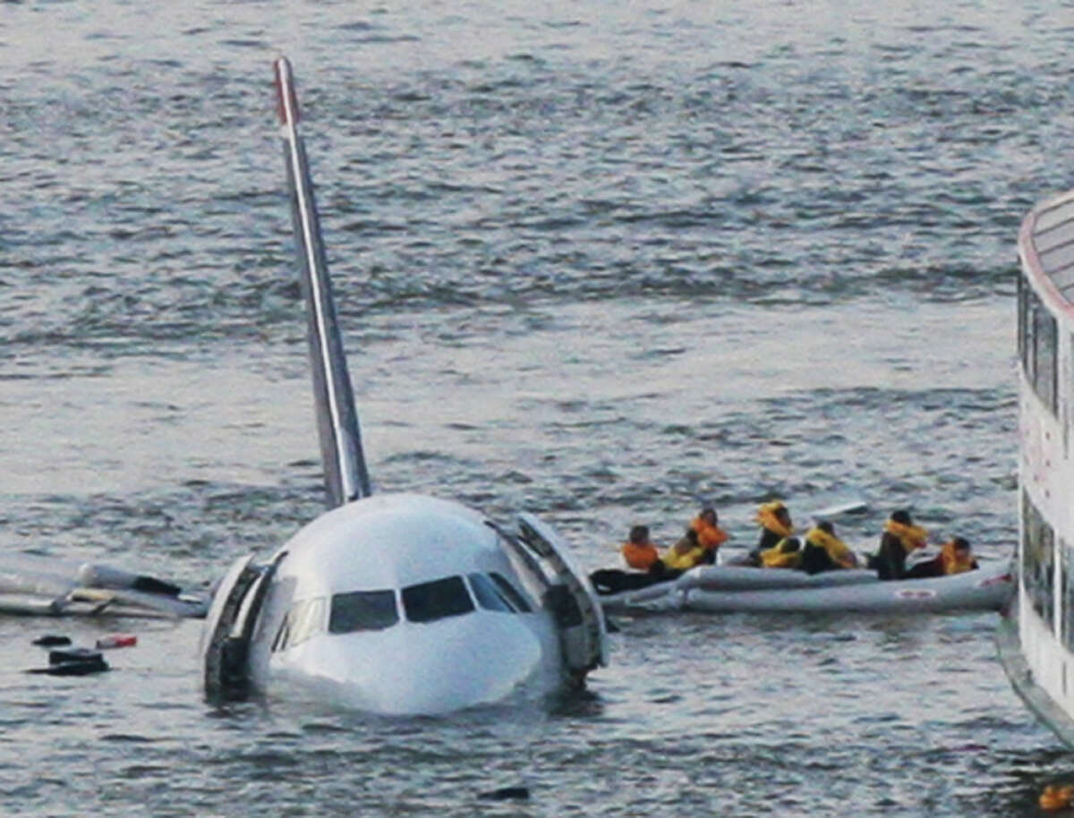 FILE - In this Jan. 15, 2009 file photo, passengers in an inflatable raft move away from an Airbus 320 US Airways aircraft that has gone down in the Hudson River in New York. More than seven years after an airline captain saved 155 lives by ditching his crippled airliner in the Hudson River, now the basis of a new movie, most of the safety recommendations stemming from the accident have yet to be followed. (AP Photo/Bebeto Matthews, File) ORG XMIT: WX201