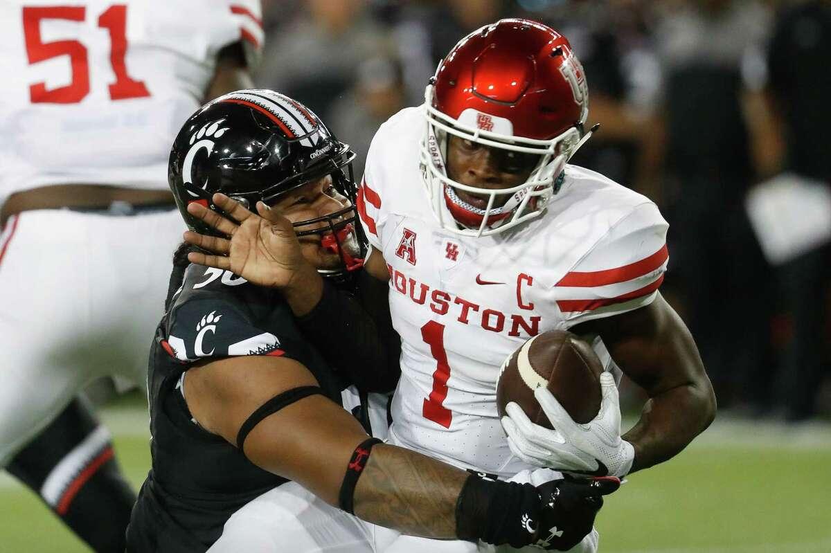 Cincinnati defensive tackle Sione Tongamoa (50) sacks Houston quarterback Greg Ward Jr. (1) during the first half of an NCAA college football game, Thursday, Sept. 15, 2016, in Cincinnati. (AP Photo/John Minchillo)