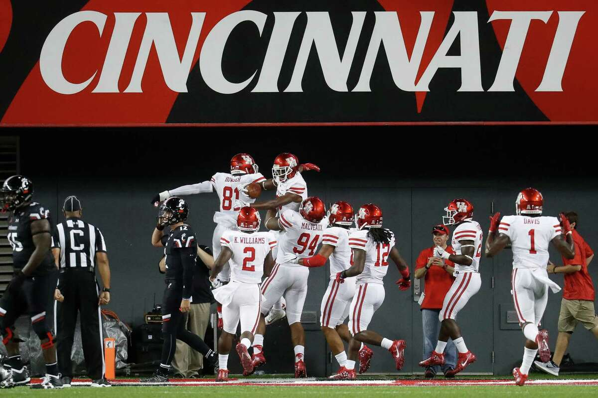 Houston cornerback Howard Wilson, top right, celebrates with linebacker Tyus Bowser (81) after scoring on an interception duriung the second half of an NCAA college football game against Cincinnati, Thursday, Sept. 15, 2016, in Cincinnati. Houston won 40-16. (AP Photo/John Minchillo)