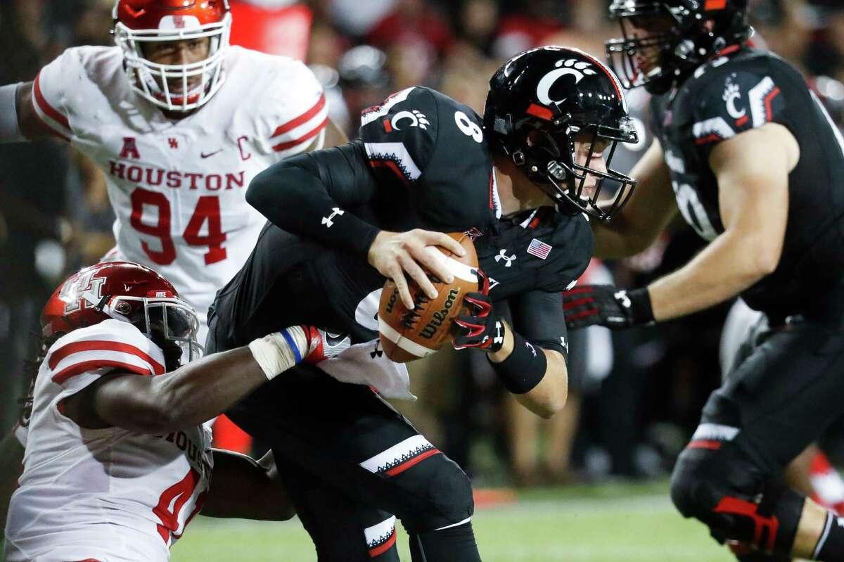 Houston linebacker Steven Taylor, left, sacks Cincinnati quarterback Hayden Moore during the second half of an NCAA college football game, Thursday, Sept. 15, 2016, in Cincinnati. Houston won 40-16. (AP Photo/John Minchillo)