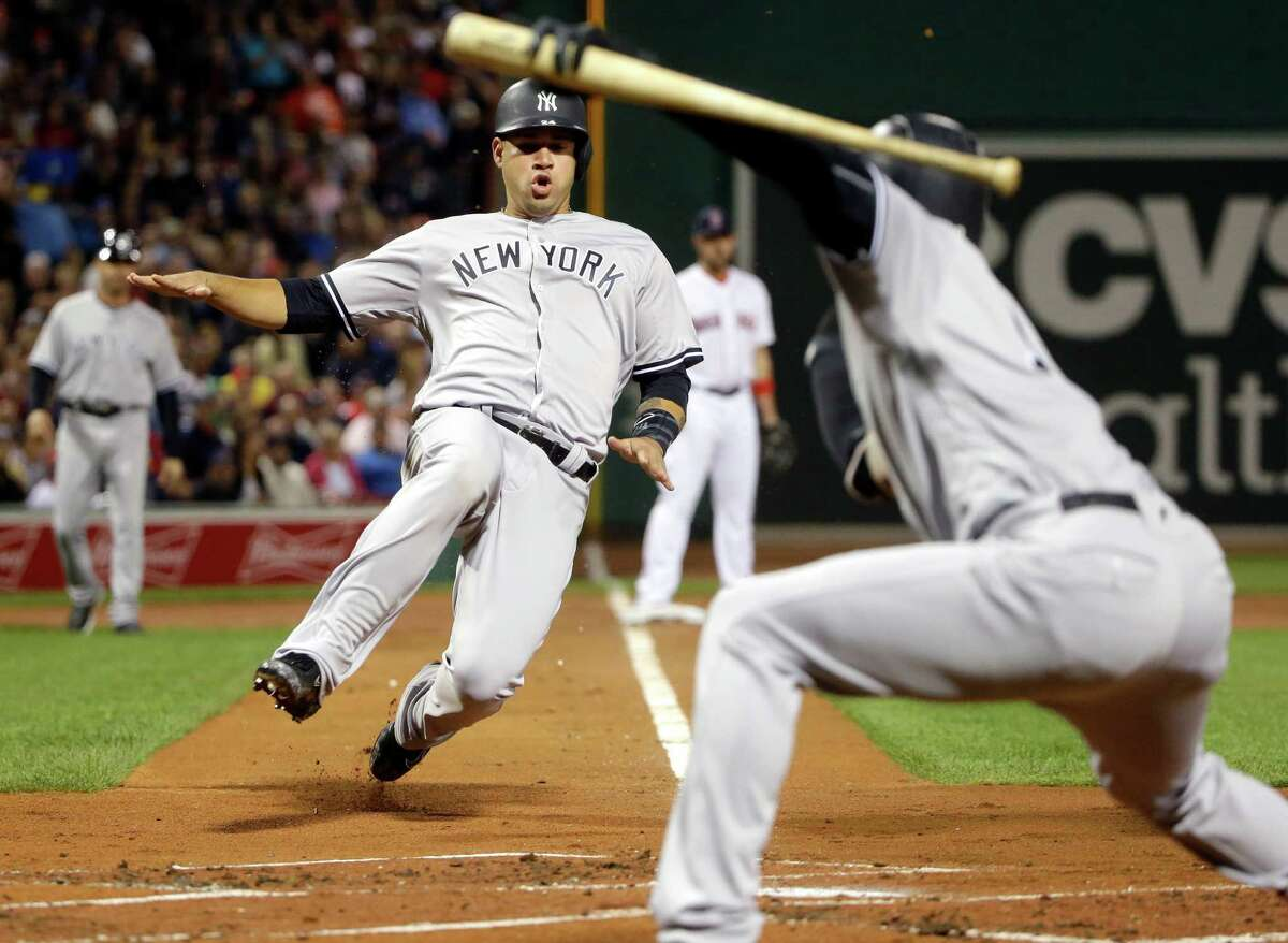 New York Yankees' Gary Sanchez slides while scoring on a sacrifice fly by Billy Butler, as teammate Didi Gregorius, right, signals to him during the first inning of a baseball game against the Boston Red Sox at Fenway Park, Thursday, Sept. 15, 2016, in Boston. (AP Photo/Elise Amendola) ORG XMIT: MAEA103