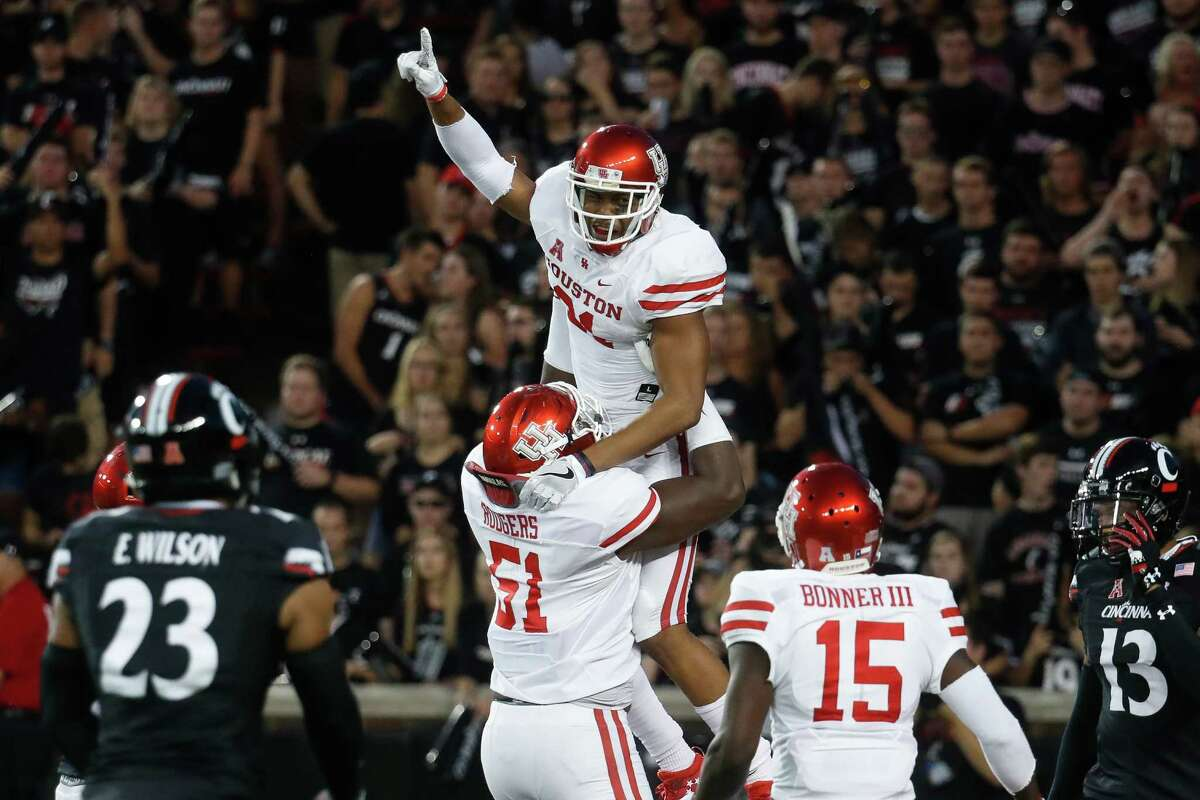 UH receiver Chance Allen, top center, celebrates the first score of the game with offensive lineman Na'Ty Rodgers (51) after catching a touchdown pass against Cincinnati. Allen grabbed a 39-yard TD pass from Greg Ward Jr. midway through the first quarter.