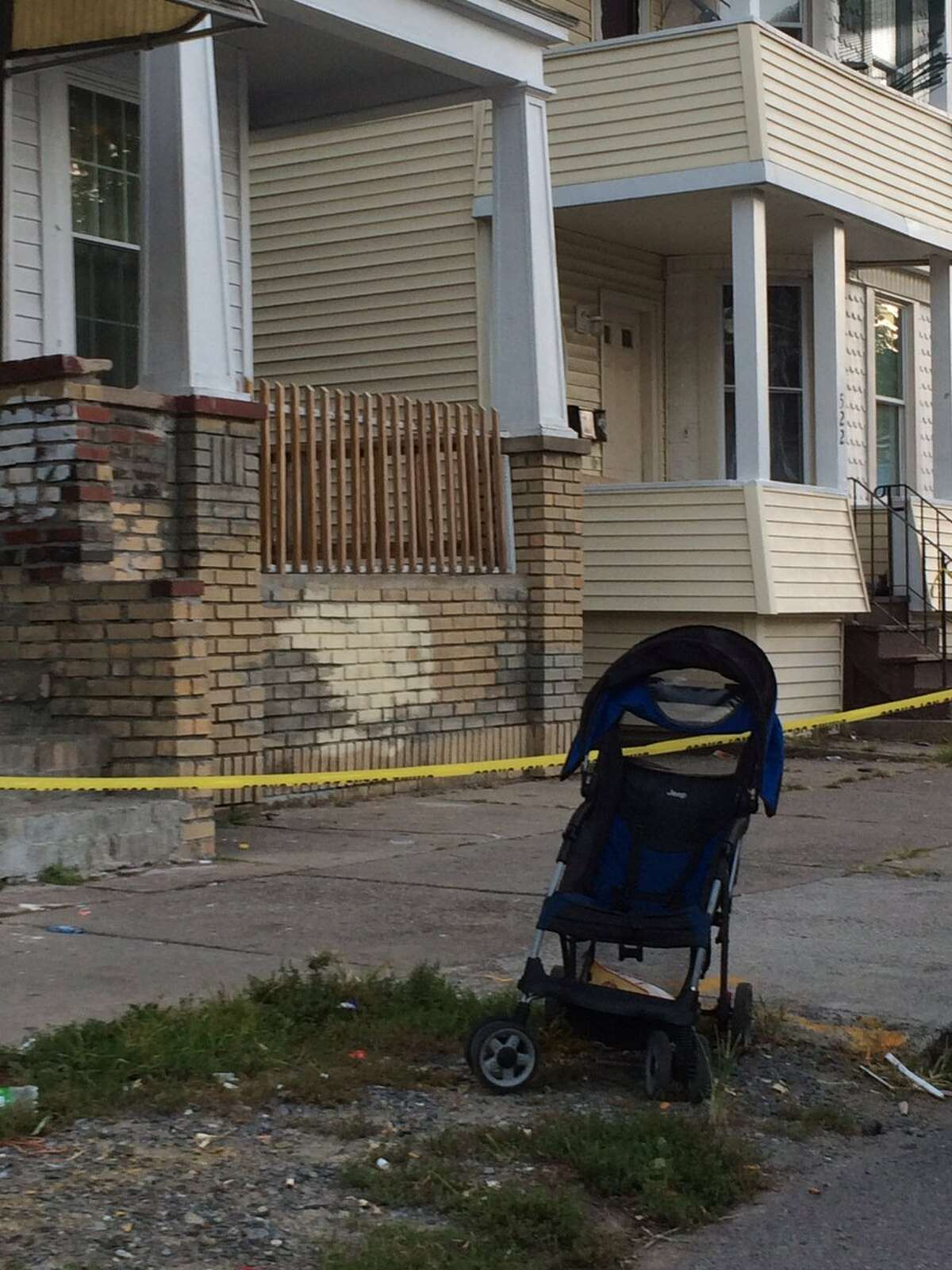 A baby stroller can be seen in the foreground as the sun rises on Schenectady Street Friday morning. Police are investigating the late-night killing of a 17-year-old girl who was shot in the head inside her second-floor apartment at 524 Schenectady St. (Emily Masters / Times Union)