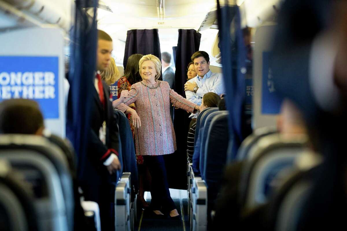 Democratic presidential candidate Hillary Clinton smiles as she speaks to aids on her campaign plane, in White Plains, N.Y., Thursday, Sept. 15, 2016, before traveling to Greensboro, N.C. for a rally. Clinton returned to the campaign trail after a bout of pneumonia that sidelined her for three days and revived questions about both Donald Trump's and her openness regarding their health. (AP Photo/Andrew Harnik) ORG XMIT: NYAH103