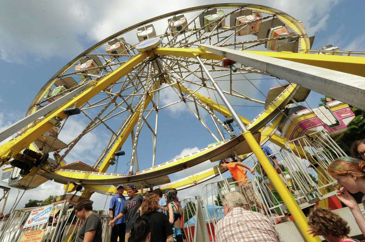 Fair goers gather for a ride on the big Ferris wheel attraction Thursday Aug. 29, 2013, at the Columbia County Fair in Chatham, N.Y. The fair runs Aug. 28-Sept. 2. (Michael P. Farrell/Times Union)