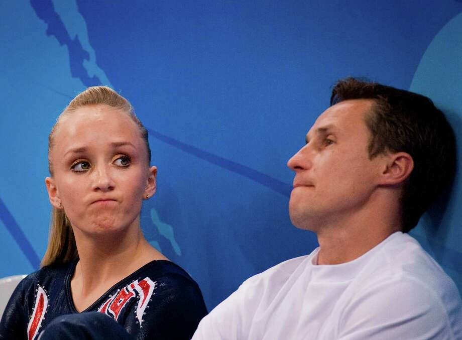 US gymnast Nastia Liukin of Parker, Texas sits with her father and coach Valeri Liukin after competing on the uneven bars during gymnastics event finals at the 2008 Summer Olympic Games, Monday, Aug. 18, 2008, in Beijing. Liukin tied with He Kexin of China on the apparatus with identical scores of 16.725 but tiebreaking procedures placed her second. Photo: Smiley N. Pool, Chronicle / Houston Chronicle