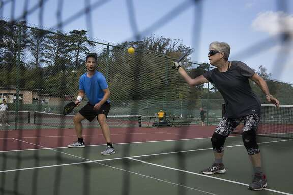 Carolyn Harvey, 70, plays doubles pickleball with Jason Keenan at the Golden Gate Park Tennis Courts on Wednesday, September 14, 2016 in San Francisco, Calif. Pickleball is a racquet sport that combines elements of tennis, ping pong and badminton. Harvey started groups playing several times a week at the tennis courts after retiring and learning the sport two years ago.