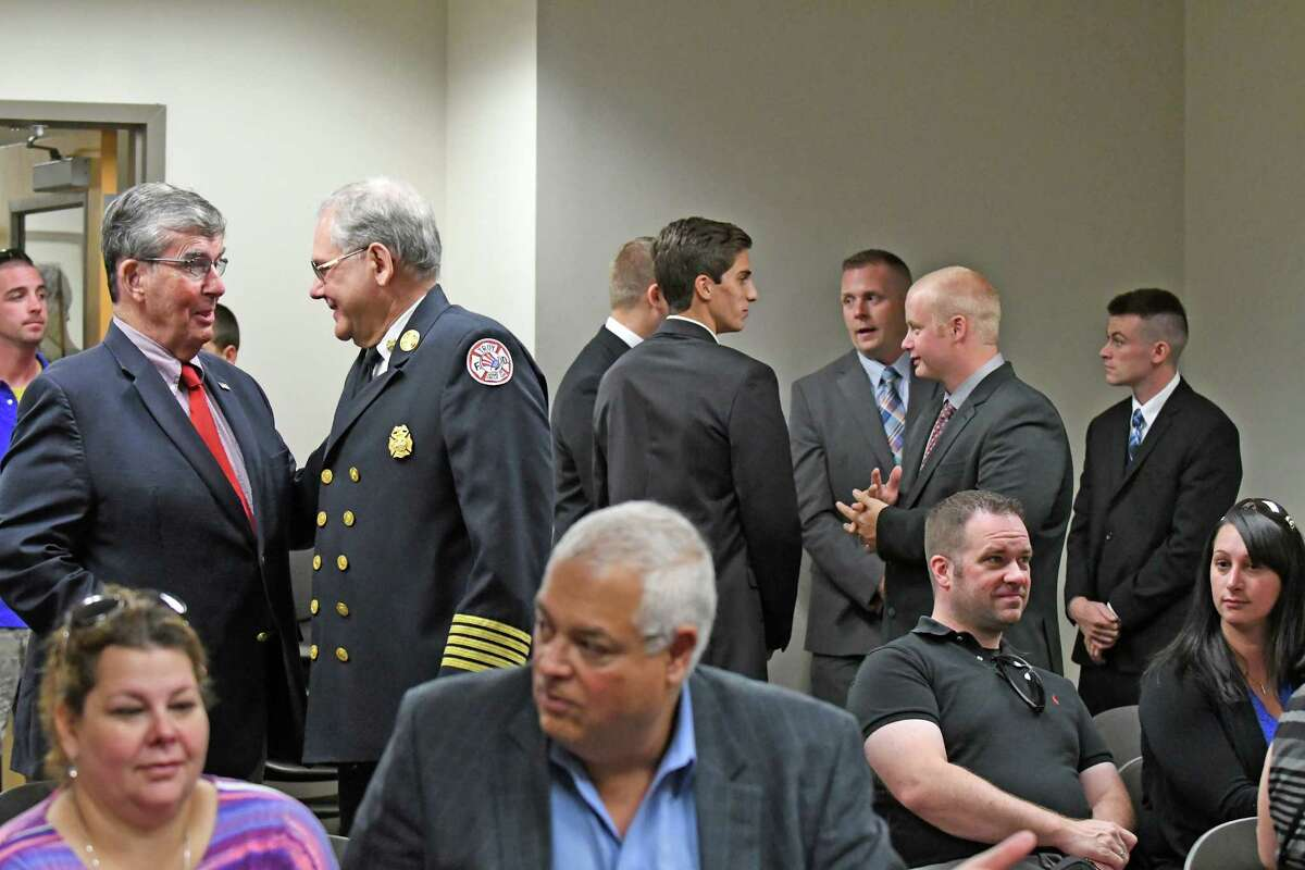 Senator Neil D. Breslin, left, talks with Fire Chief Thomas Garrett as five new firefighters were sworn in during a ceremony at Troy City Hall on Friday Sept. 16, 2016 in Troy, N.Y. (Michael P. Farrell/Times Union)
