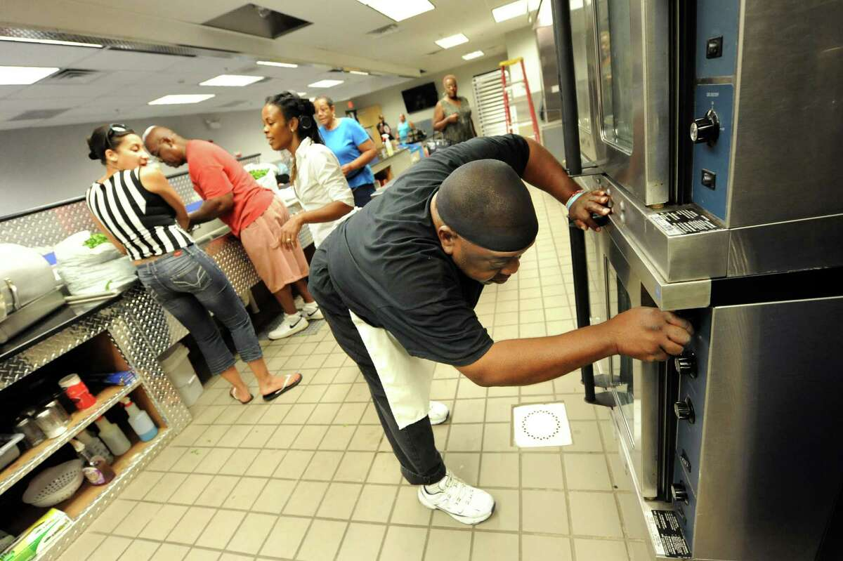 AVillage member Lennie Golden, right, checks the ovens before he starts to cook in preparation for Mississippi Day on Thursday, Sept. 17, 2015, at Victory Church Dream Center in Albany, N.Y. (Cindy Schultz / Times Union archive)