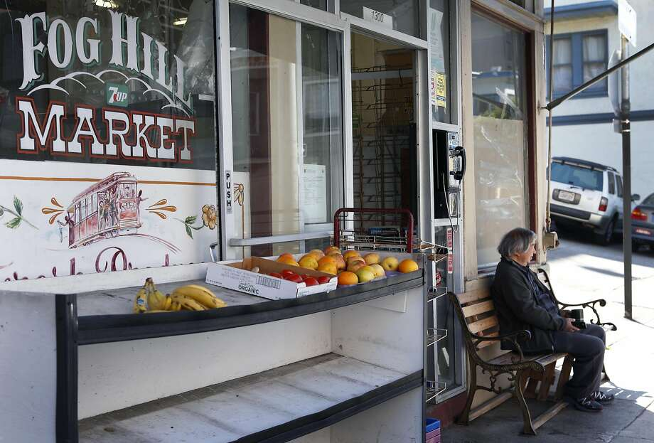 Local neighbor Myron Mu watches the world go by as shopkeeper Hanna Chedyak clears out what's left inside his Fog Hill Market at Kearny and Green streets. Photo: Paul Chinn, The Chronicle