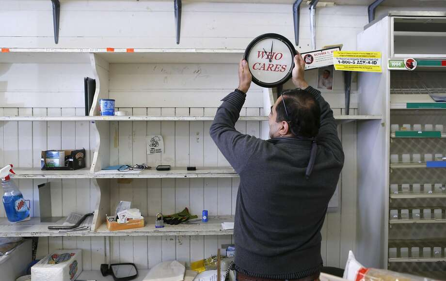 Hanna Chedyak removes a wall clock from bare shelves inside his Fog Hill Market, from which he is being evicted by his landlord after running the corner store on Telegraph Hill for more than 20 years. Photo: Paul Chinn, The Chronicle
