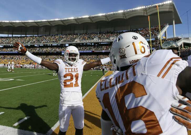 Texas cornerback Duke Thomas (21) comes over to celebrate with safety DeShon Elliott and other teammates after the final play of the NCAA college football game against Baylor Saturday, Dec. 5, 2015, in Waco, Texas. Texas won 23-17. (AP Photo/LM Otero)