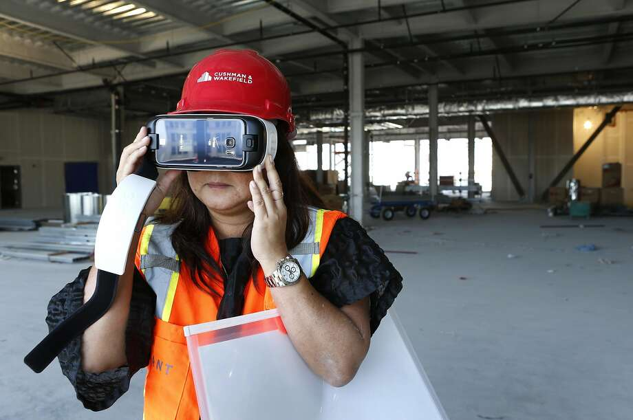 Kazuko Morgan, who's trying to lure retail tenants to the center, uses a vir tual reality viewer for pros pective clients to see the finished project. Photo: Paul Chinn, The Chronicle