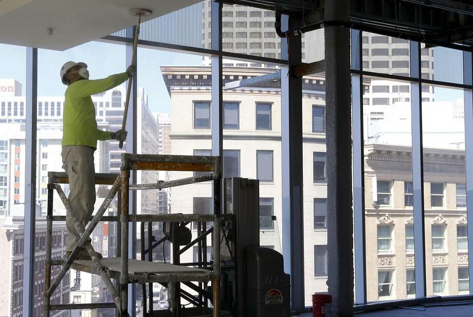 A worker sands a section of ceiling in front of the full-length windows at the rebranded 6x6 retail, food and entertainment center that previously was called Market Street Place. Photo: Paul Chinn, The Chronicle