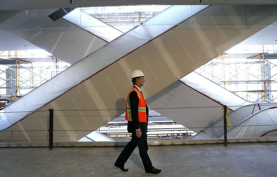 Chris Maguire, Cypress Equities CEO, walks past scissoring escalators in the nearly built 6x6 retail and entertainment center. Photo: Paul Chinn, The Chronicle