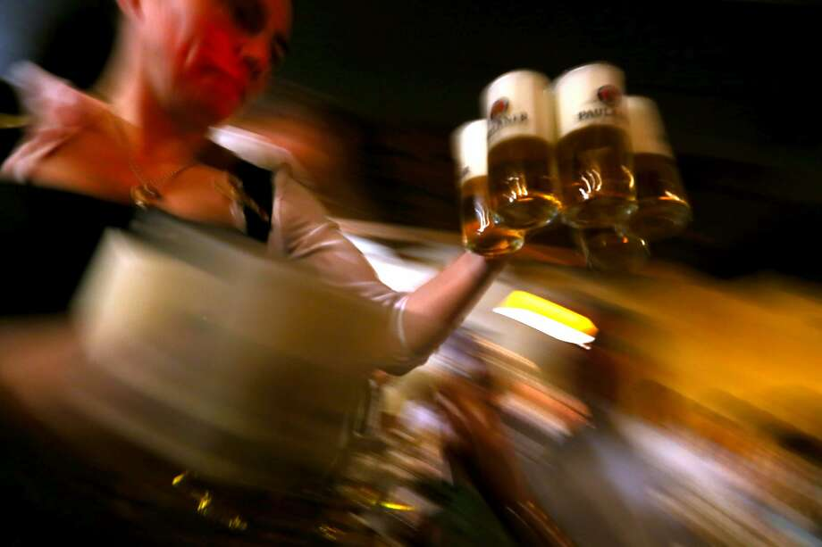 A waitress brings glasses of beer to the heads of the six Munich breweries as well as the owners of the Oktoberfest tents. Photo: Alexander Hassenstein/Getty Images