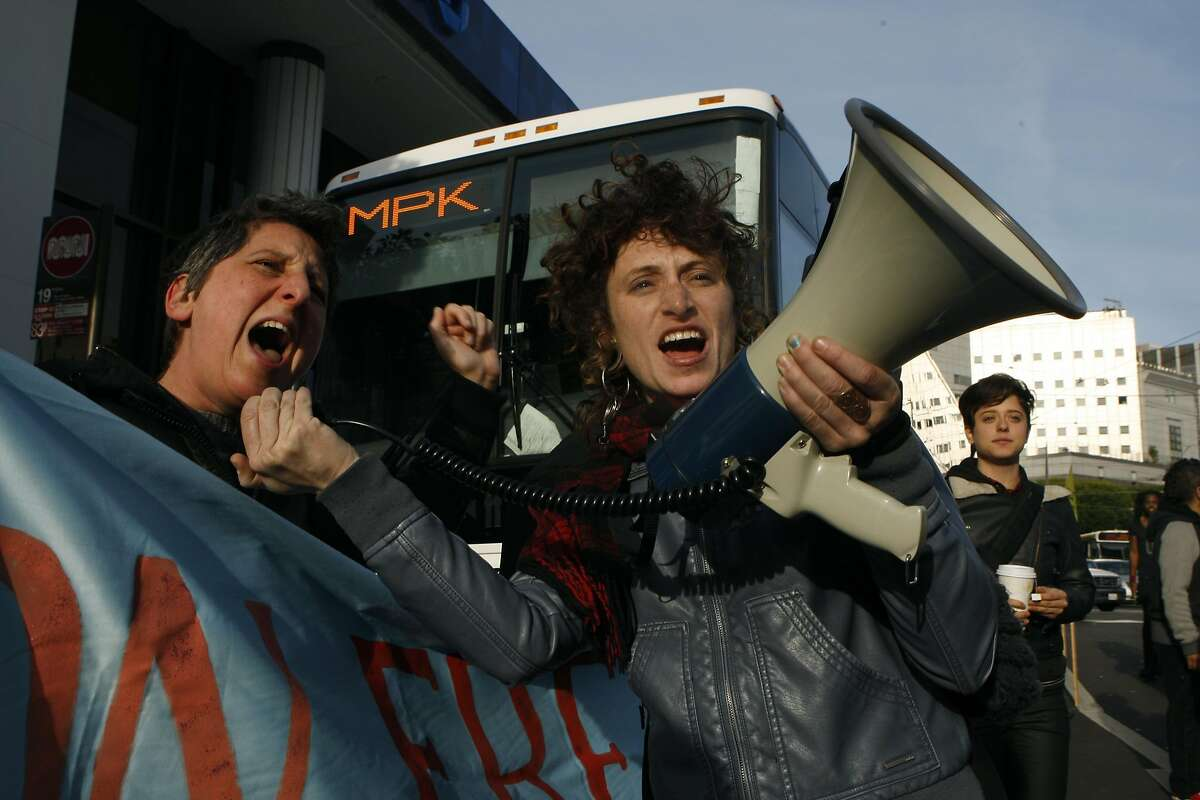 Sara Shortt (left) from the Housing Rights committee of San Francisco and activist Erin McElroy (right) block a Facebook bus heading to Menlo Park on 8th at Market streets in San Francisco, Calif., on Tuesday, January 22, 2014. The San Francisco Metropolitan Transportation Agency votes on an 18-month pilot plan allowing Google buses to use designated Muni bus stops to pick up and drop off tech commuters to Silicon Valley.