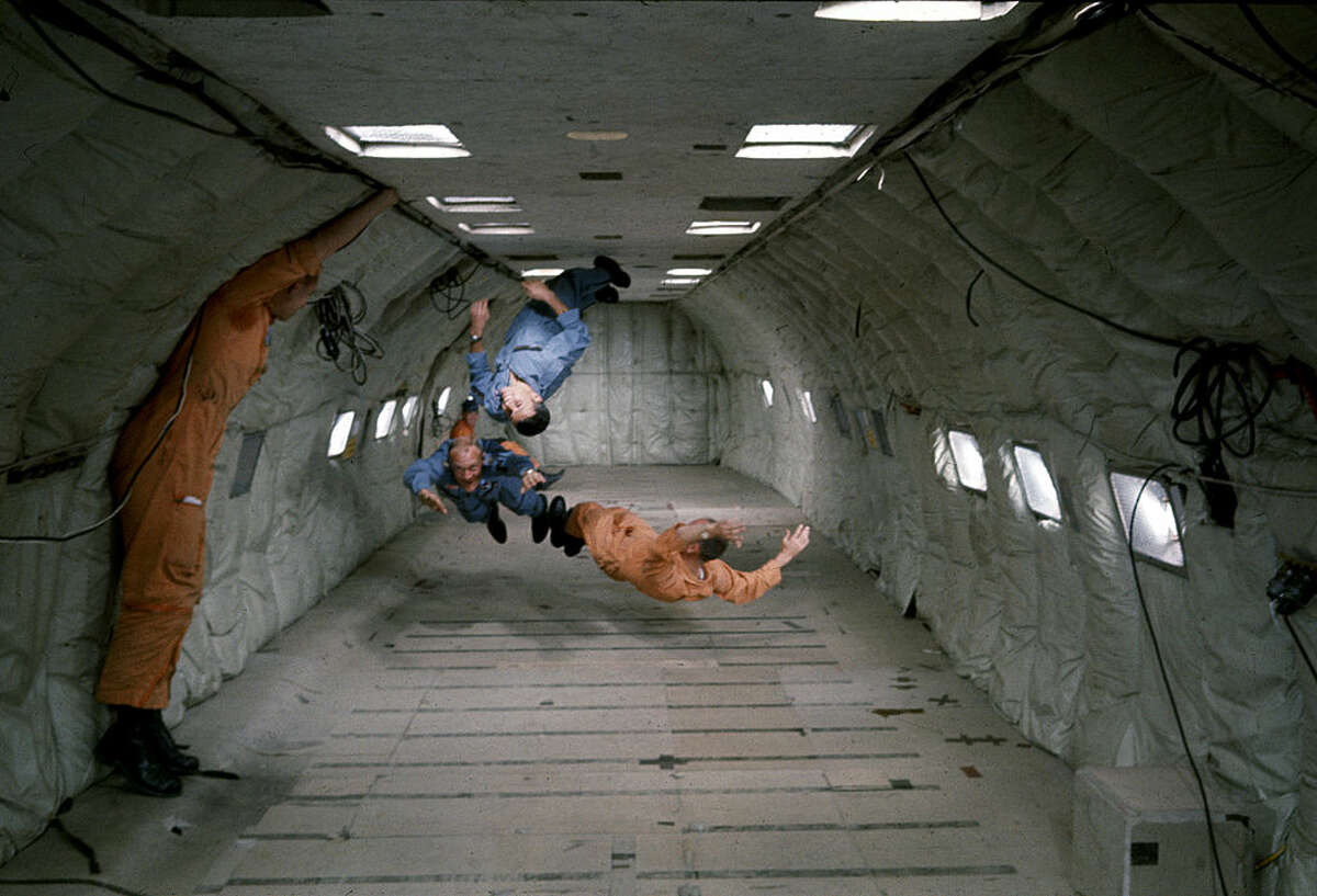 As a technician watches at left, American astronauts Charles Bassett (1931 - 1966) (upsidedown, in blue), Buzz Aldrin (bottom, in blue), and Theodore Freeman (1930 - 1964) (right, in orange) experience weightlessness in a reduced gravity aircraft (probably a converted KC-135 Stratotanker) as part of their NASA mission training, 1964. (Photo by Ralph Morse/The LIFE Picture Collection/Getty Images)