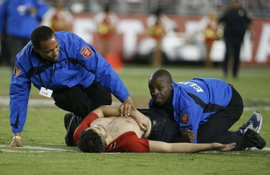A spectator who stormed the field is tackled by security officers during the 49ers-Rams game at Levi's Stadium on Monday. Photo: Tony Avelar, Associated Press