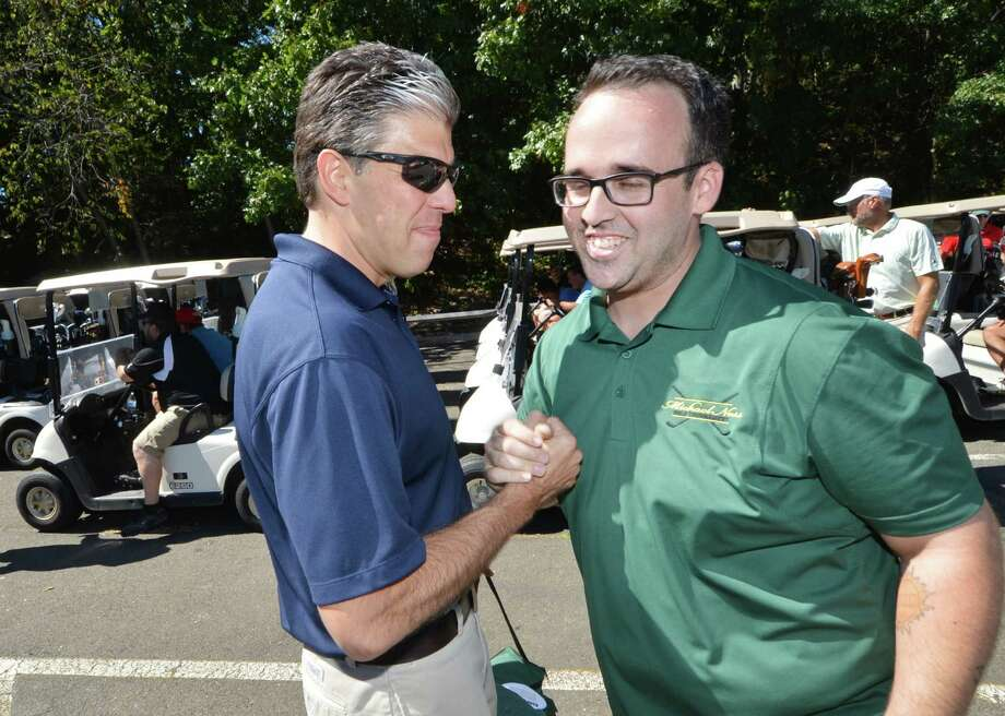 Steve Jakob, President of the Bridgeport Hospital Foundation congratulates Matt Ness, Michael's brother at the start of the 3rd annual Michael Ness Play it Forward Golf Tournament at Oak Hills Park in Norwalk Conn. on Monday September 12, 2016. The charity event benefits the Connecticut Burn Center at Bridgeport Hospital where Michael was treated for burns he suffered in a Norwalk house fire in 2013. Photo: Alex Von Kleydorff / Hearst Connecticut Media / Connecticut Post