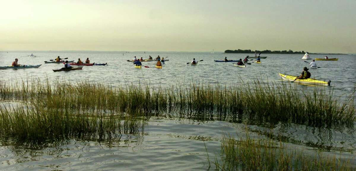 Kayakers and rowers make their way out to the start line for the Soundkeepers Lighthouse to Lighthouse Race 2004 at Compo Beach. Kathleen O'Rourke/Staff photo