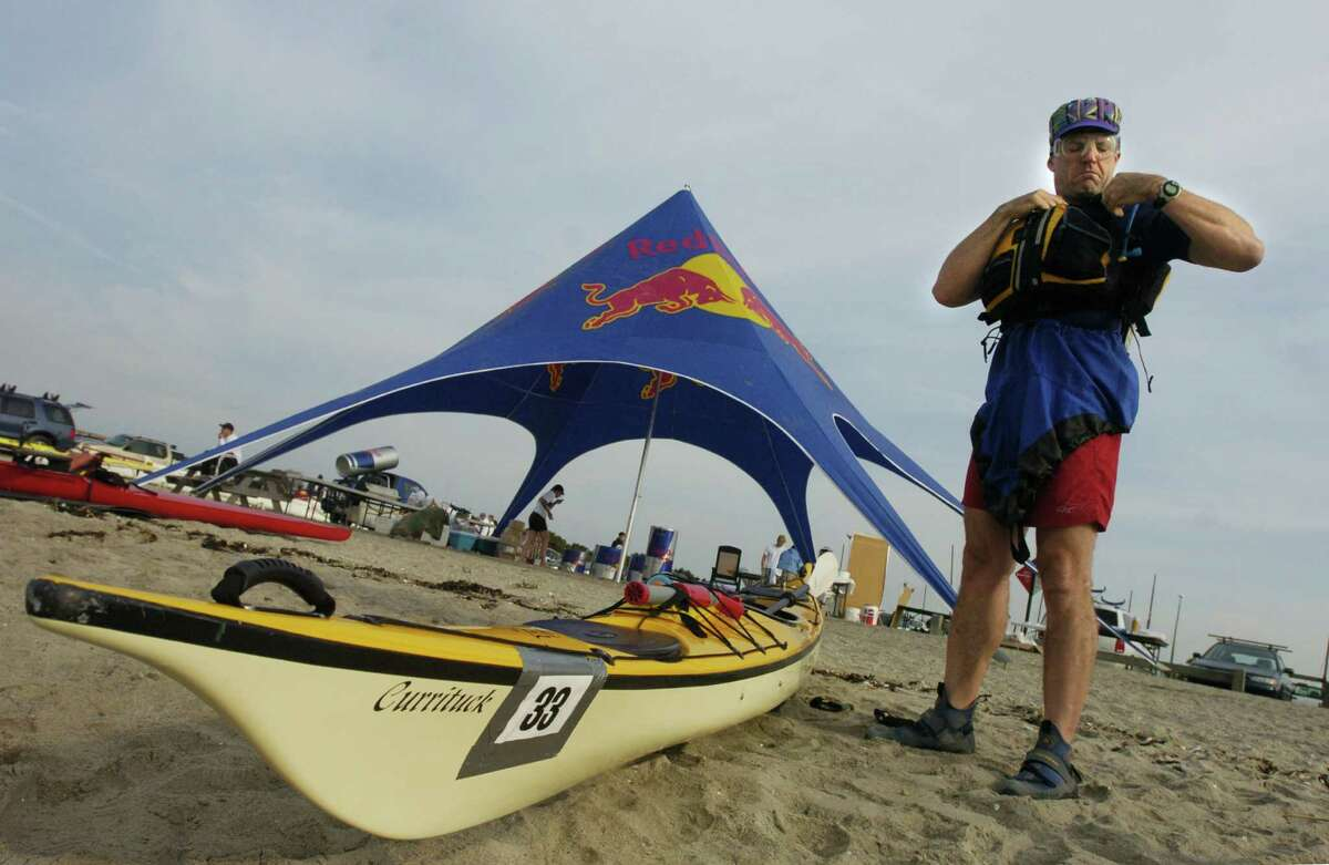 Sean Milano, of Wellesley Mass., prepares to enter the water for the Soundkeepers Lighthouse to Lighthouse Race 2004 at Compo Beach. Kathleen O'Rourke/Staff photo
