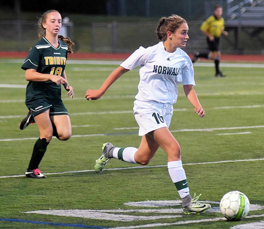 Norwalk's Julia Sferlazza, right, races with the ball to get away from Trinity Catholic defender Hannah Tedesko during the first half of Thursday night's FCIAC girls soccer game at Testa Field in Norwalk. Sferlazza netted three goals to lead Norwalk to a 6-0 win. Photo: John Nash / Hearst Connecticut Media / Norwalk Hour