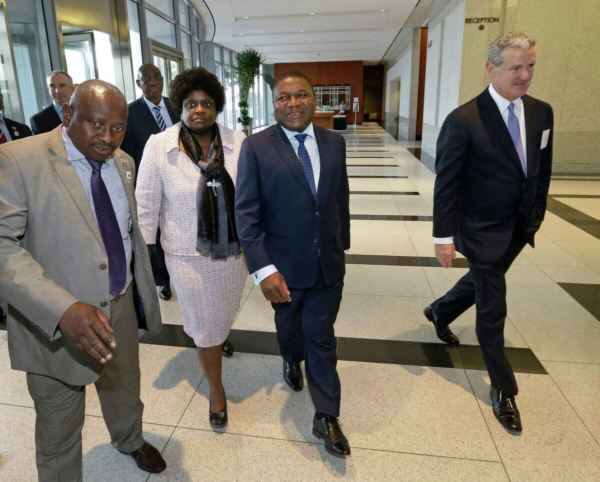 Mozambique's president, Filipe Nyusi, center, arrives at Anadarko Petroleum Corp.'s Allison Tower in The Woodlands with Mozambique's first lady, Isaura Ferrao Nyusi, and Anadarko CEO Al Walker, right.