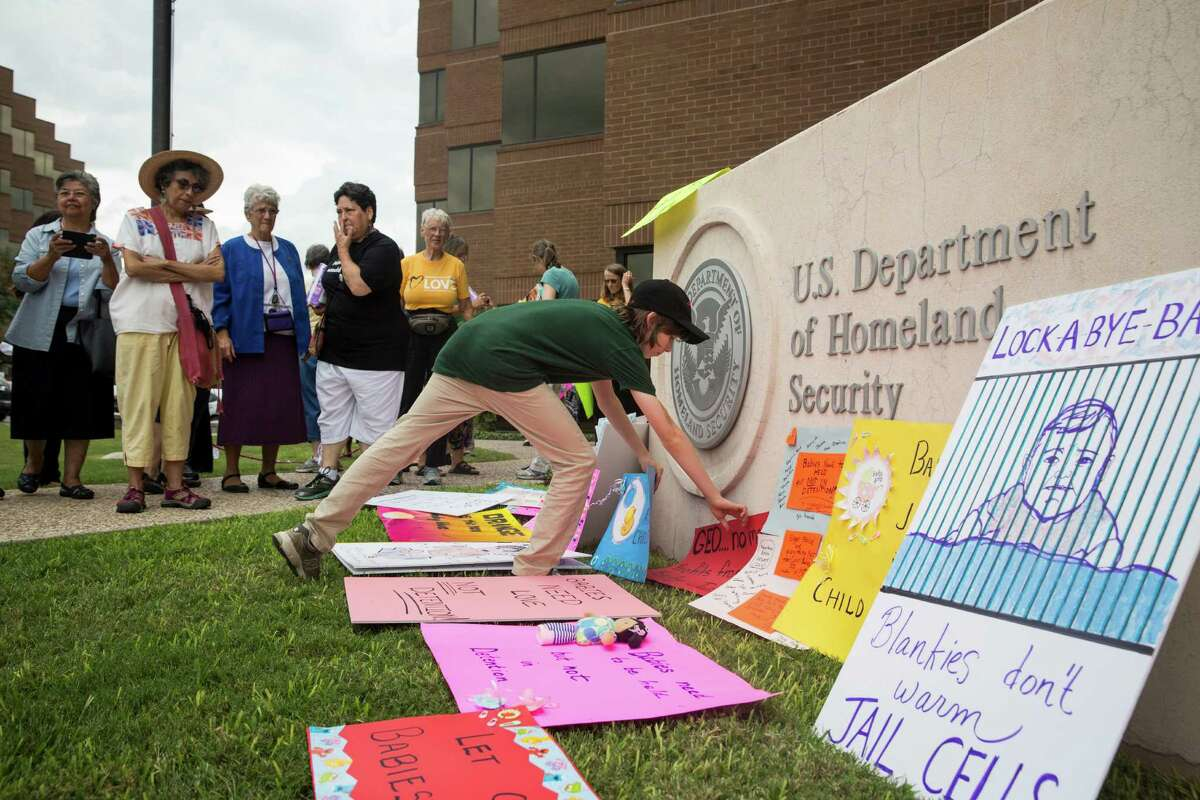 Benjamin Welchman, 12, delivers a sign to the San Antonio U.S. Immigration and Customs Enforcement office during a rally in San Antonio, Texas on Aug. 30. The rally protested the thousands of women and children being held in family detention in Karnes and Dilley facilities south of San Antonio.