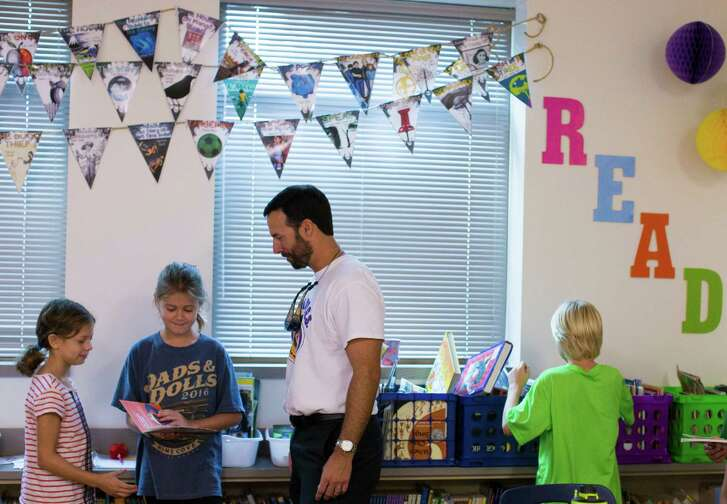 Lance Terveen, center, a father with the WATCH D.O.G.S. program, helps Bella Smith, left, and Sarah Hickman pick books for reading time Wednesday at Rummel Creek Elementary.