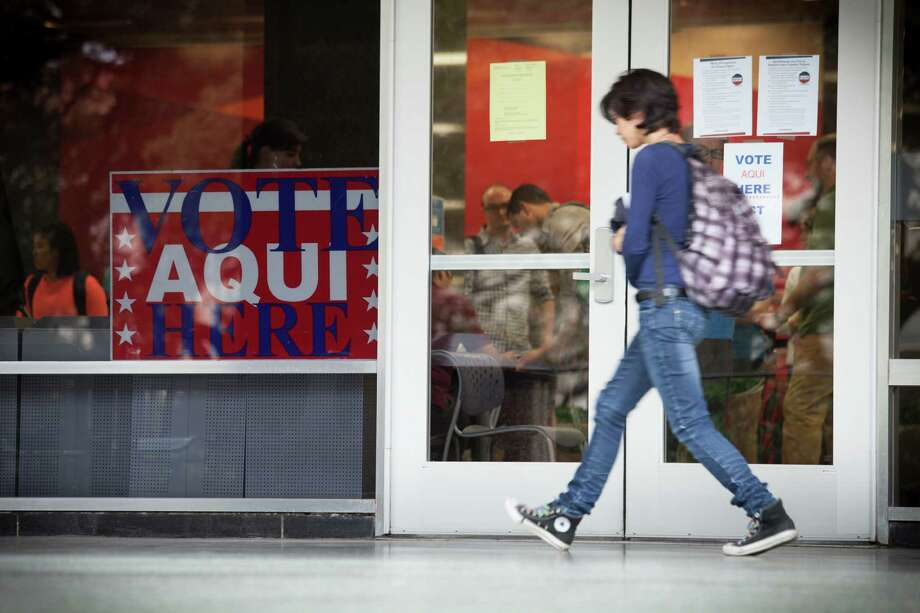 Voter I.D. requirements are posted on the doors of a polling place on the University of Texas campus. A reader condemns state officials for trying to inhibit voter registration. Photo: MICHAEL STRAVATO /New York Times / NYTNS
