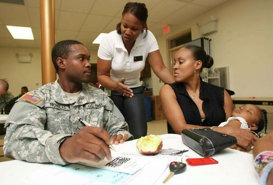 An Army Community Services financial educator talks with a military family at Fort Bliss. The conservative G Fund is the most popular investment choice of middle-class military families. Photo: Associate Press /File Photo / FR39270AP