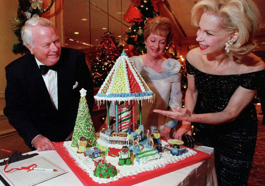 """CONTACT FILED:  TREES OF HOPE-HOUSTON (LEFT to RIGHT) Allan and Gloria King, and Lynn Wyatt check out one of the auction items, a gingerbread construction called """"Joy Ride"""" designed by Jeff Davis High School's 1st period culinary arts class, at the Trees of Hope annual benefit for Star of Hope held at the Westin Oaks Hotel in Houston, Texas Thursday evening November 29, 2001.   HOUCHRON CAPTION (12/05/2001):  The holiday spirit prevailed at the annual Trees of Hope gala at the Westin Oaks Hotel on Thursday. Chairs Allan and Gloria King join honorary chair Lynn Wyatt, right, in admiring one of the numerous gingerbread houses up for auction. More than 400 guests bid on decorated Christmas trees, holiday wreaths and the gingerbread and helped raise more than $400,000 for Star of Hope. Highlight of the benefit was a performance by Rosemary Clooney. Photo: D. FAHLESON, Staff / Houston Chronicle"""
