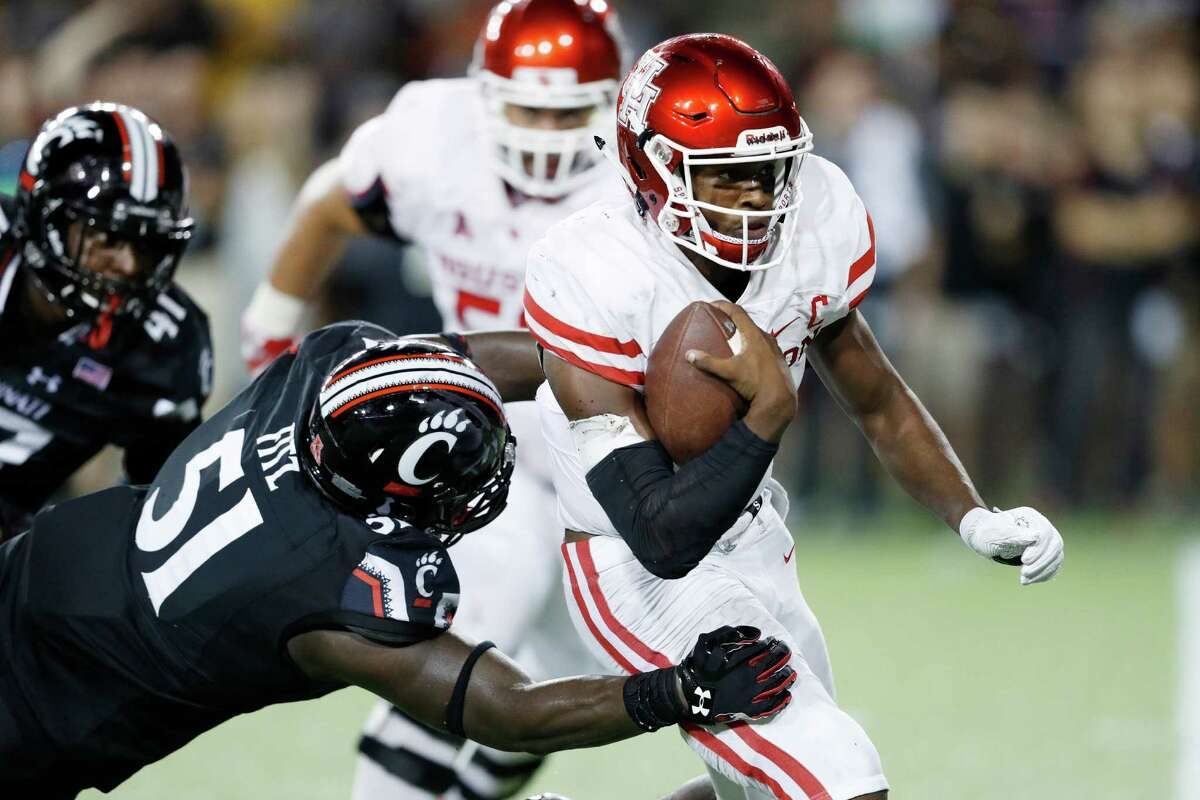 UH quarterback Greg Ward Jr. breaks a tackle attempt by Cincinnati's Kimoni Fitz for a 12-yard touchdown in the fourth quarter of the Cougars' win in the conference opener Thursday night.