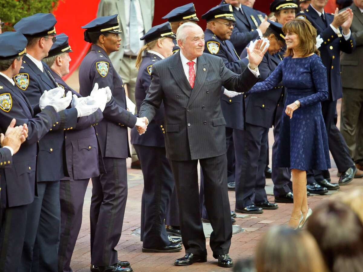 New York Police Department Commissioner William Bratton, center, accompanied by his wife Rikki Klieman, shake hands and acknowledged the applause of officers and commanders in dress blue uniforms during a ceremony, as he left police headquarters on his last day on the job, Friday Sept. 16, 2016, in New York. (AP Photo/Bebeto Matthews) ORG XMIT: NYBM302
