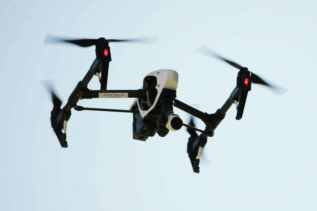 FILE - In this April 14, 2016 file photo, a drone captures videos and still images of an apartment building in Philadelphia. Federal aviation officials say so many people are registering drones and applying for drone pilot licenses, they wonder if there will eventually be millions of drones crowding the nation's skies. (AP Photo/Matt Rourke, File) ORG XMIT: WX104