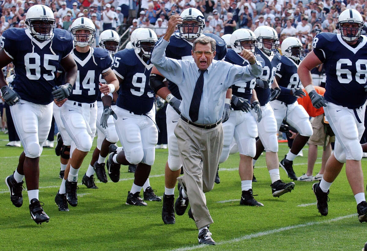 FILE - In this Sept. 4, 2004 file photo, Penn State coach Joe Paterno leads his team onto the field before an NCAA college football game against Akron in State College, Pa. As Penn State's athletic department finalizes details for how to honor the 50th anniversary of Joe Paterno?'s first win, hundreds of the late coach?'s former players were on their way to town to attend a private reunion planned for Friday at the school?'s baseball stadium. (AP Photo /Carolyn Kaster, File) ORG XMIT: NY179