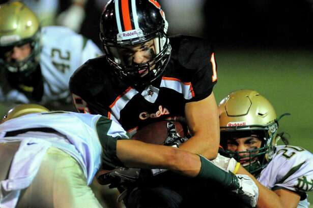 Shelton's Joe Zoppi is pulled down from behind by Notre Dame of West Haven's Jordan Gargiulo and another player in front during football action in Shelton, Conn., on Friday Sept. 16, 2016.