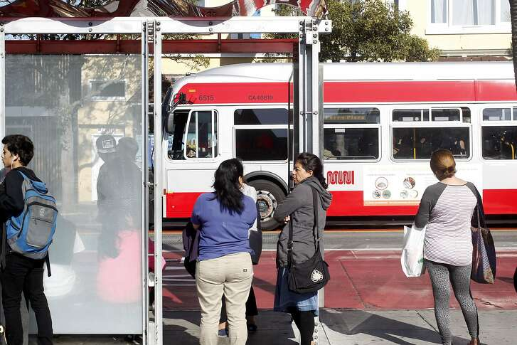 Passengers wait to board an outbound Muni bus at 24th and Mission streets in San Francisco, California on Friday, September 15,  2016.