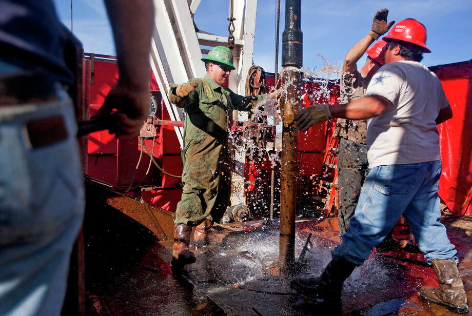 Guy Cummings (left), Carl Merworth (center, rear) and Desiderio Castillo (right) attach a 90-foot section of pipe onto the end of an active drill pipe on the drilling floor of Robinson Drilling rig #4 on Wednesday, Feb. 17, 2016, in Midland County.  James Durbin/Reporter-Telegram Photo: James Durbin / © 2016 Midland Reporter Telegram. All Rights Reserved.