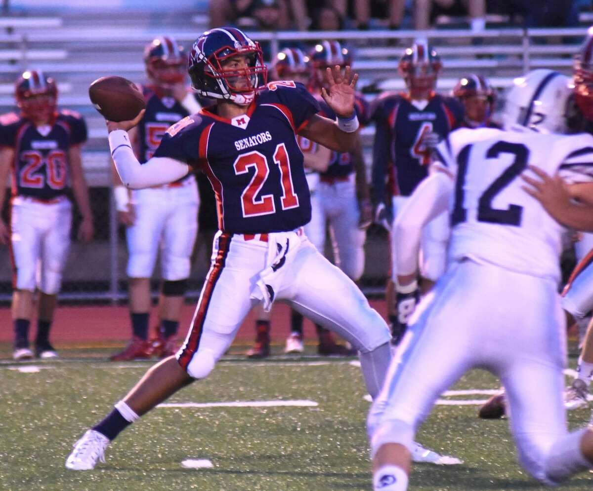 Brien McMahon quarterback Chris Druin (21) rears back and throws a 56-yard touchdown pass to Eric Day during the first quarter of Friday's FCIAC football game against Wilton at Casagrande Field in Norwalk. Wilton defeated McMahon 28-7.