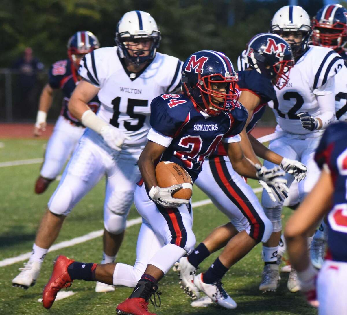 Brien McMahon's Eric Day (24) looks for running room during the first quarter of Friday's FCIAC football game against Wilton at Casagrande Field in Norwalk. Wilton defeated McMahon 28-7.