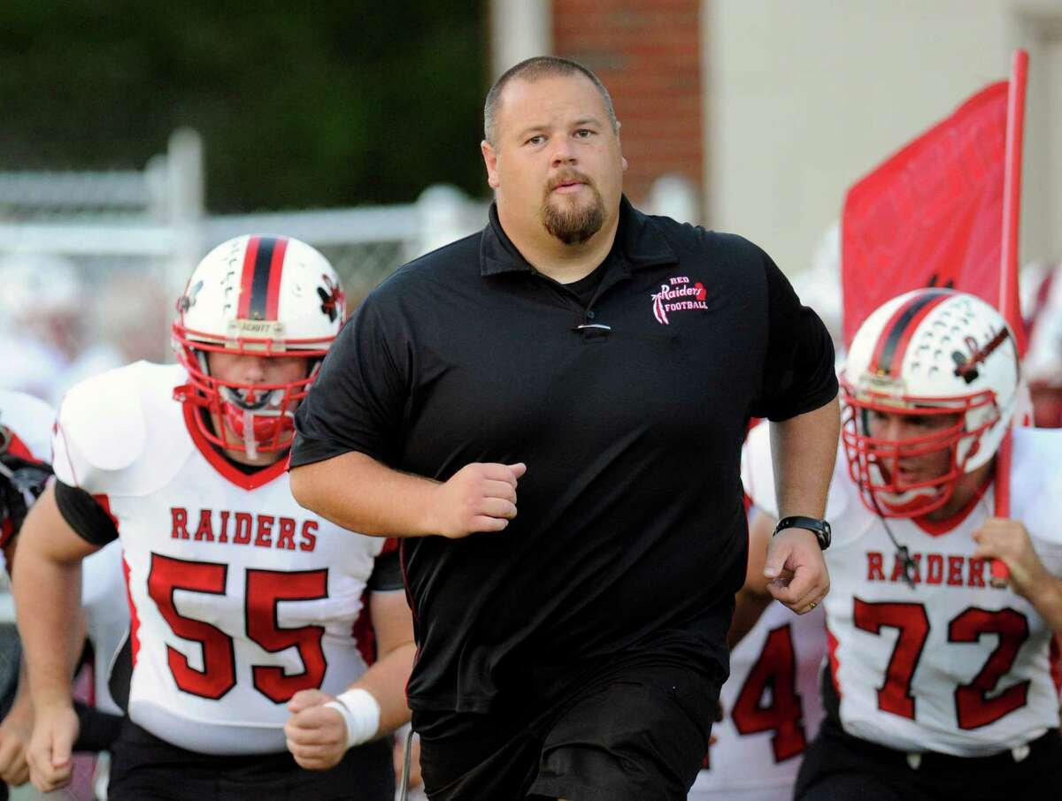 Mechanicville head coach Erik Smith leads his team onto the field against Holy Trinity during a Section II Class C high school football game in Troy, N.Y., Friday, Sept. 16, 2016. (Hans Pennink / Special to the Times Union) ORG XMIT: HP101