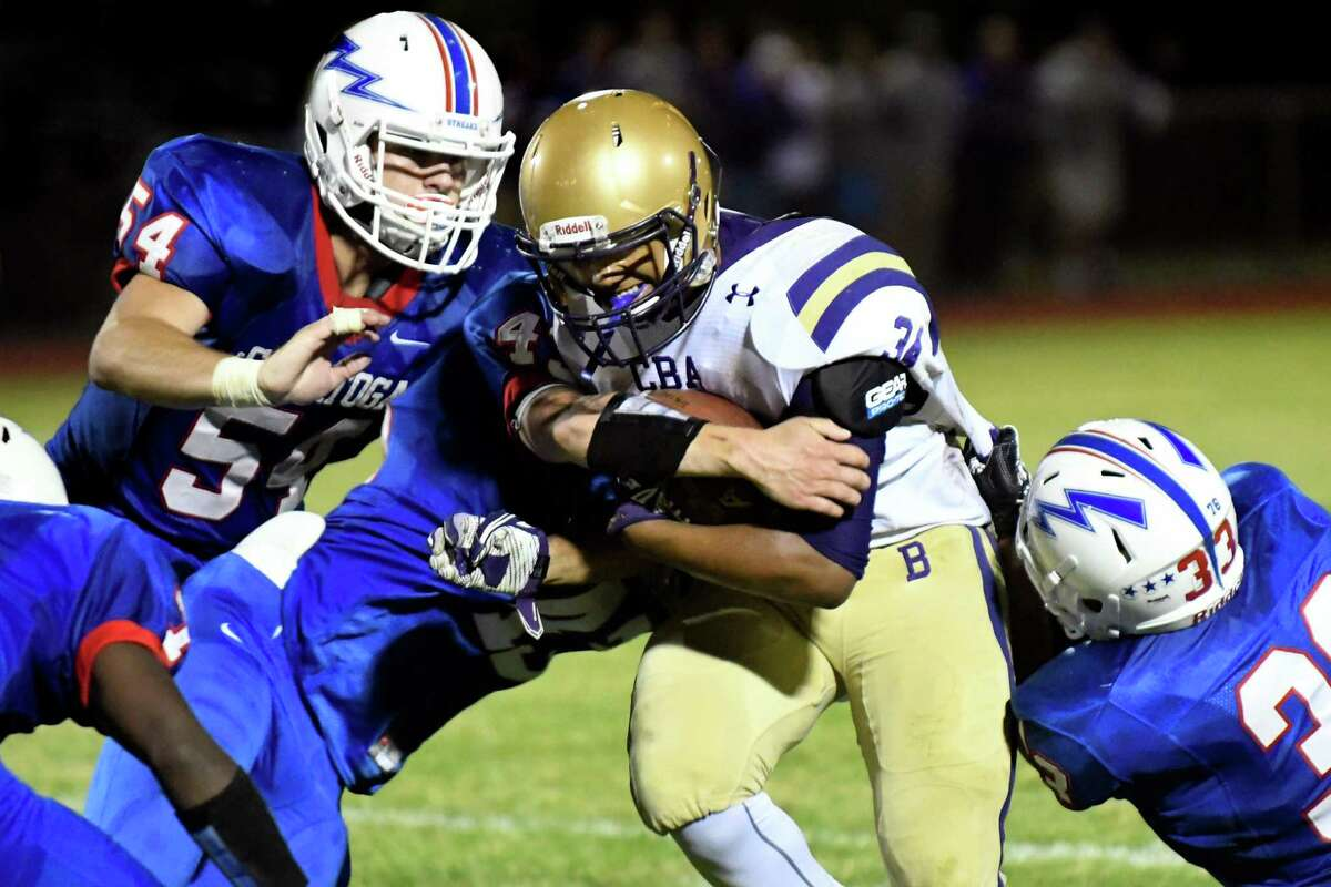 CBA's Brian Tucker, center, fights off Saratoga's defense during their football game on Friday, Sept. 16, 2016, at Saratoga Springs High in Saratoga Springs, N.Y. (Cindy Schultz / Times Union)