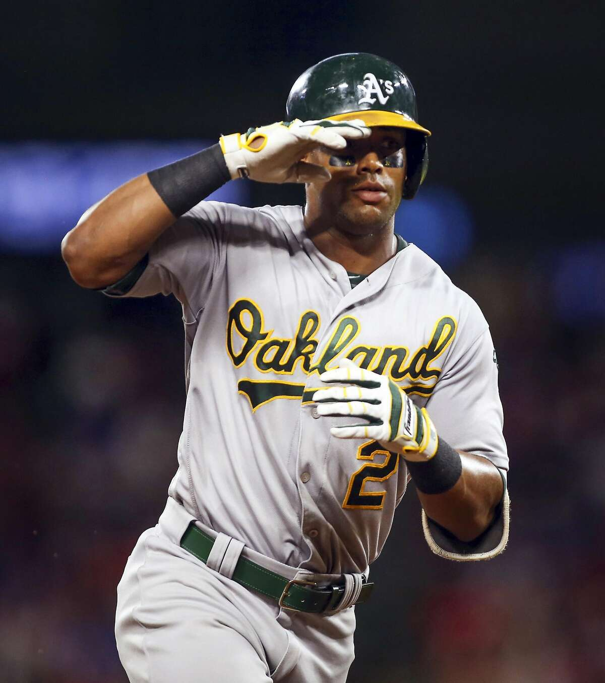 The Oakland Athletics' Khris Davis salutes the dugout as he rounds third base after a two-run home run in the fourth inning against the Texas Rangers at Globe Life Park in Arlington, Texas, on Friday, Sept., 16, 2016. (Richard W. Rodriguez/Fort Worth Star-Telegram/TNS)