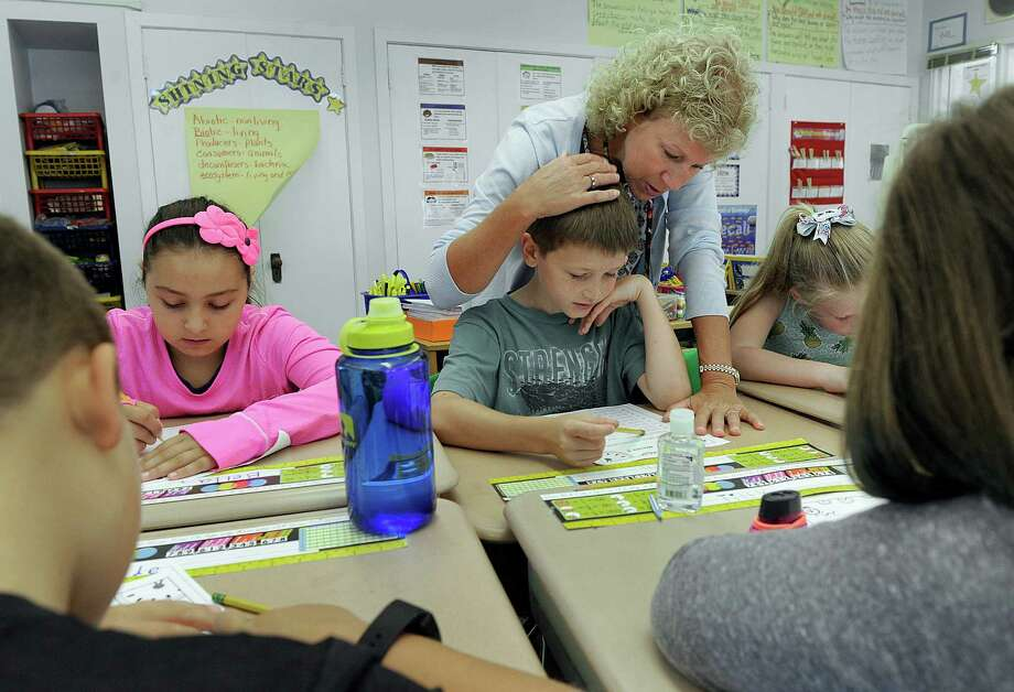 Fourth-grade teacher Pam Lucchesi, looks over Tim Shyshkop's shoulder as the class works on reading and writing at Booth Free School in Roxbury on Thursday. Photo: Carol Kaliff / Hearst Connecticut Media / The News-Times