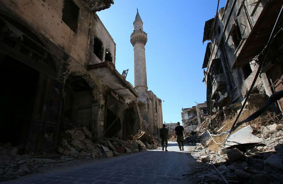 Syrian soldiers walk through a damaged area Friday in the government-held side of Aleppo. Despite a cease-fire, aid convoys have been unable to reach the rebel-held parts of the city. Photo: YOUSSEF KARWASHAN, AFP/Getty Images
