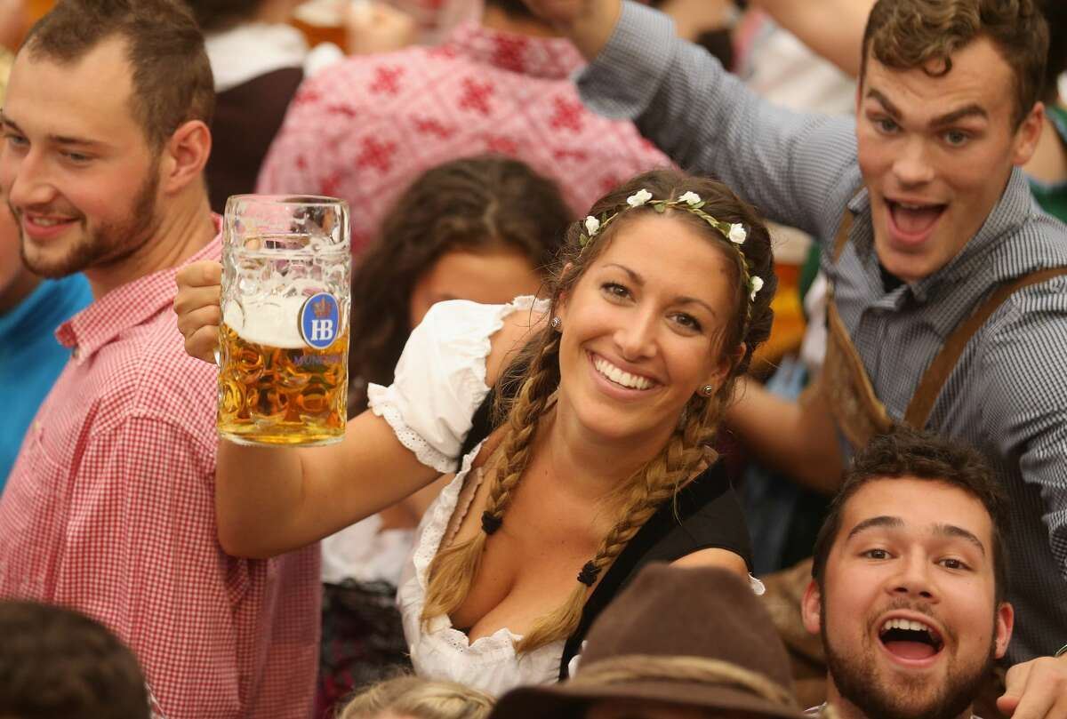 Visitors hold up one-litre glasses of beer to kick off the 2016 Oktoberfest beer festival in the Hofbraeu tent at Theresienwiese on September 17, 2016 in Munich, Germany.