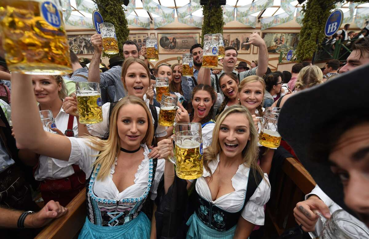 Visitors salute with beer mugs during the opening of the Oktoberfest beer festival in a festival tent at the Theresienwiese in Munich, southern Germany, on September 17, 2016.